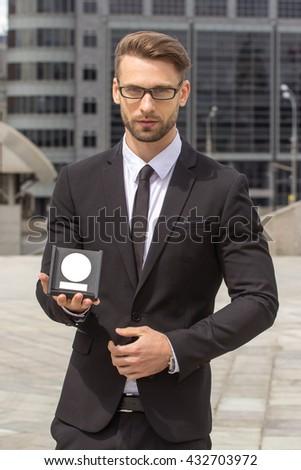 Happy Businessman with award on urban background - stock photo