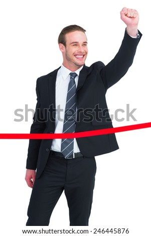 Happy businessman with clenching fist crossing the finish line n white background - stock photo