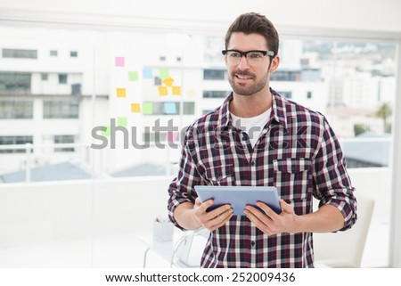 Happy businessman with glasses holding tablet in the office - stock photo