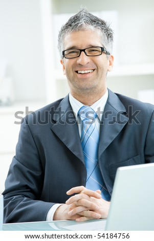 Happy businessman with gray hair and glasses sitting at office desk, smiling and looking at camera.