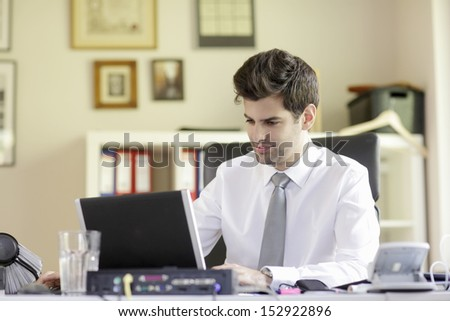 Happy businessman with laptop in his office. Shallow Focus. - stock photo