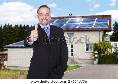 Happy Businessman With Thumbs Up Standing In Front Of House - stock photo