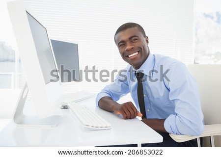 Happy businessman working at his desk in his office