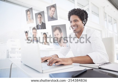 Happy businessman working at his desk wearing headset against profile pictures - stock photo