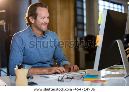 Happy businessman working on computer in creative office