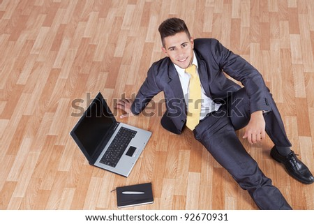 Happy businessman working with his laptop sited on the house floor - stock photo