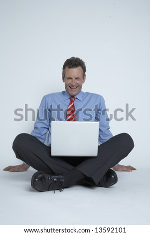 Happy Businessman works on laptop - stock photo