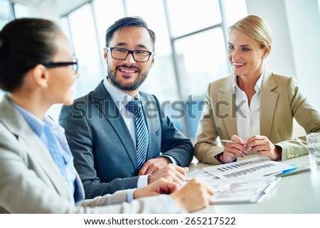 Happy businessmen and two pretty employees communicating at meeting - stock photo