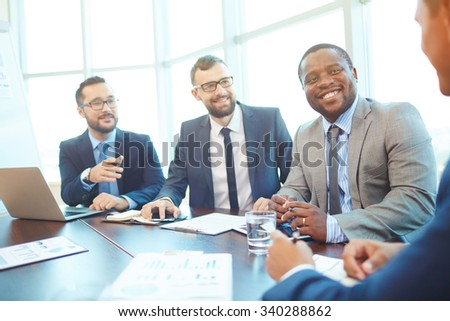 Happy businessmen discussing seminar or negotiating with partner