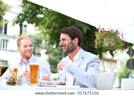 Happy businessmen having food at sidewalk cafe - stock photo