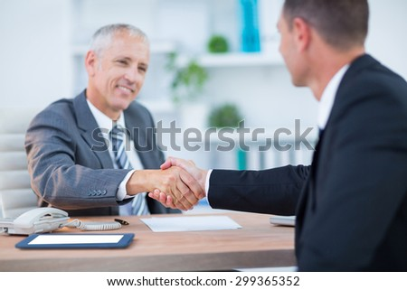 Happy businessmen shaking hands in the office - stock photo