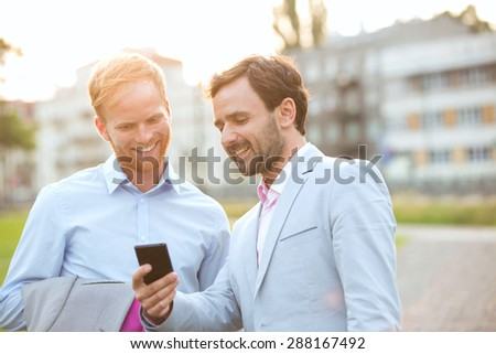 Happy businessmen using mobile phone in city - stock photo