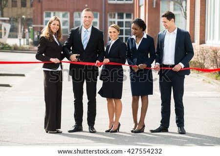 Happy Businesspeople At Opening Cutting Ribbon With Scissor