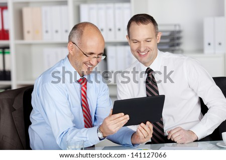 Happy businesspeople browsing through tablet in the office - stock photo