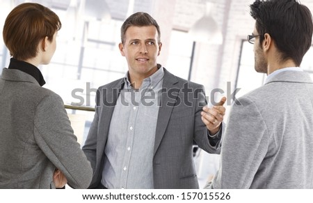 Happy businesspeople discussing at office. - stock photo
