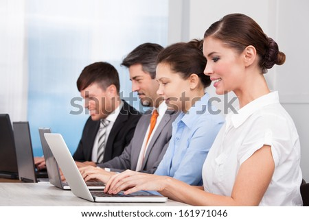 Happy Businesspeople In A Row Working Together At Office - stock photo