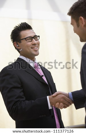Happy businesspeople shaking hands with each other at office - stock photo
