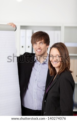 Happy businesspeople standing in front of a flipchart - stock photo