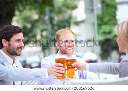 Happy businesspeople toasting beer glasses at outdoor restaurant - stock photo
