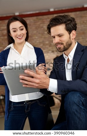 Happy businesspeople using tablet computer, smiling. - stock photo