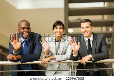 happy businesspeople waving hands in office - stock photo