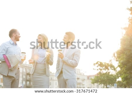 Happy businesspeople with disposable cups talking against clear sky on sunny day - stock photo