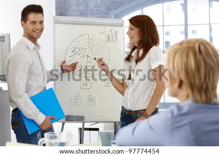 Happy businesspeople working with whiteboard, doing presentation, using diagram. - stock photo