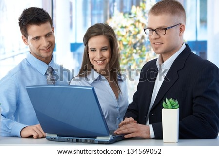 Happy businessteam working together in office, using laptop computer, smiling. - stock photo