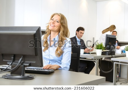 Happy businesswoman at her desk, with people working at the background - stock photo