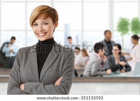 Happy businesswoman at office people working in background. - stock photo