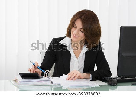 Happy Businesswoman Calculating Tax At Desk In Office - stock photo