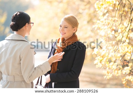 Happy businesswoman conversing with colleague at park on sunny day - stock photo