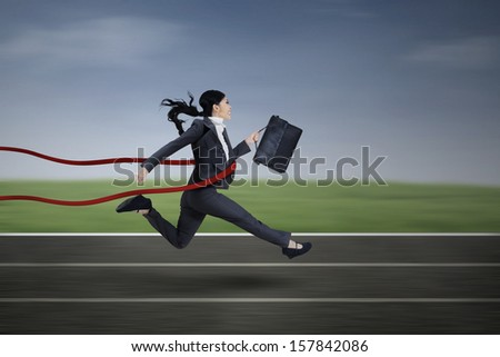 Happy businesswoman crossing finish line during race - stock photo