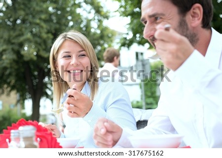 Happy businesswoman eating food with colleague at sidewalk cafe - stock photo
