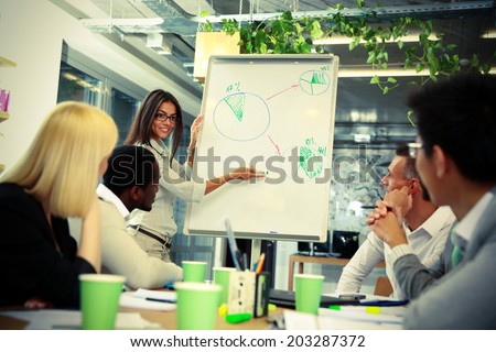 happy businesswoman explaining graph to his colleagues - stock photo