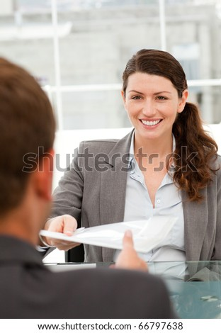 Happy businesswoman giving a paper to a male colleague during a meeting - stock photo