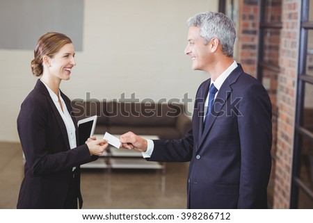 Happy businesswoman giving business card to client in office - stock photo