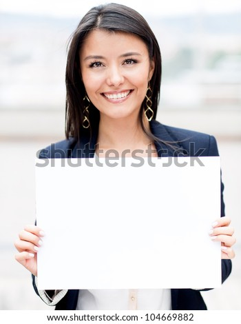 Happy businesswoman holding a white banner and smiling - stock photo