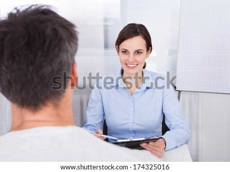 Happy Businesswoman Holding Clipboard With Pen In Front Of Businessman
