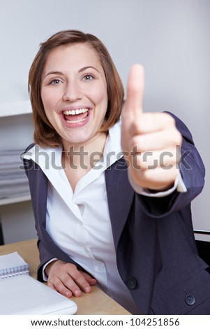 Happy businesswoman holding thumbs up at her desk in the office - stock photo