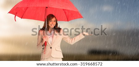 Happy businesswoman holding umbrella against cloudy sky - stock photo