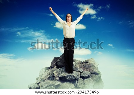happy businesswoman in formal wear raised hands up on top of mountain over blue sky with clouds