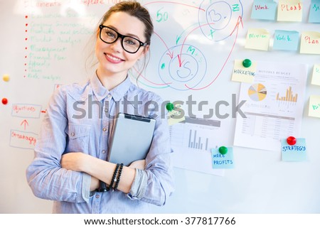 Happy businesswoman in glasses looking at camera with whiteboard on background - stock photo