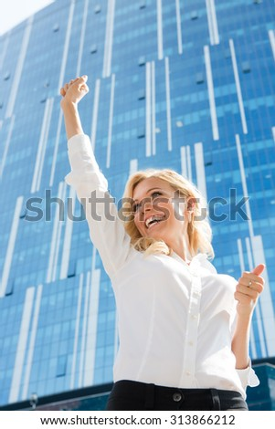 Happy businesswoman is the winner. Beautiful lady in white blouse raised her hand and smiling because of success. - stock photo