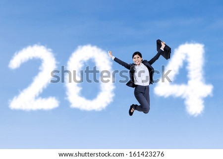 Happy businesswoman jumping with 2014 by clouds - stock photo