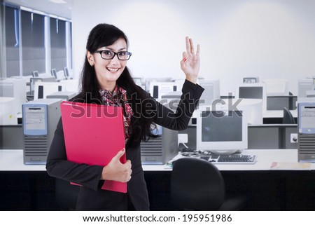 Happy businesswoman making an ok sign. shoot in the office - stock photo