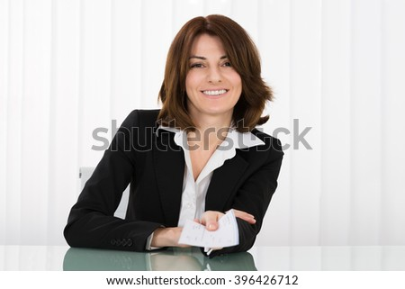 Happy Businesswoman Offering Pay Cheque In Office - stock photo