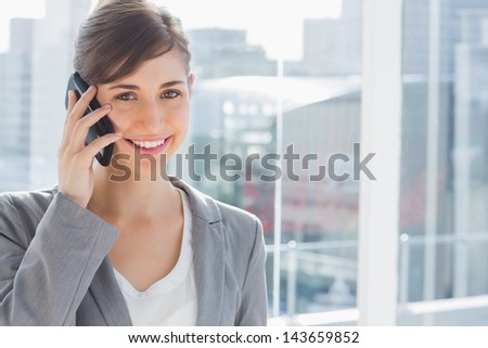 Happy businesswoman on the phone looking at camera - stock photo