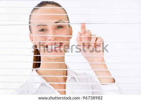 Happy businesswoman peeking through a venetian blind in an office - stock photo