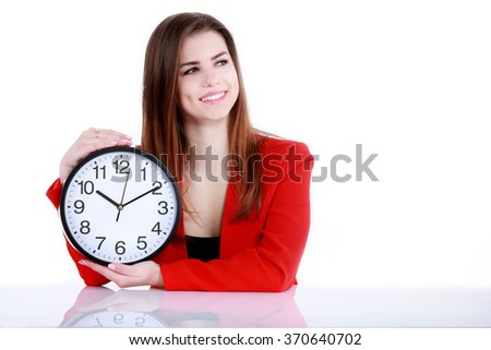 Happy businesswoman pointing on a clock by a desk.